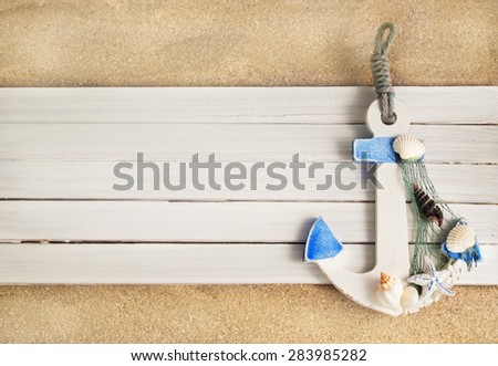 Little decorative anchor on a wooden planks over sandy background.