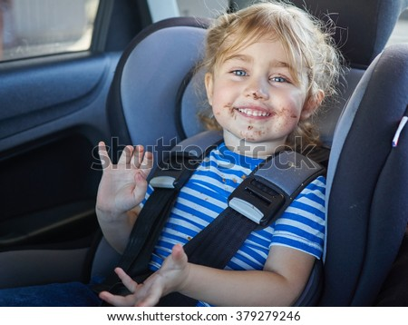 Little dirty girl , baby in a safety car seat. Safety and security - stock photo