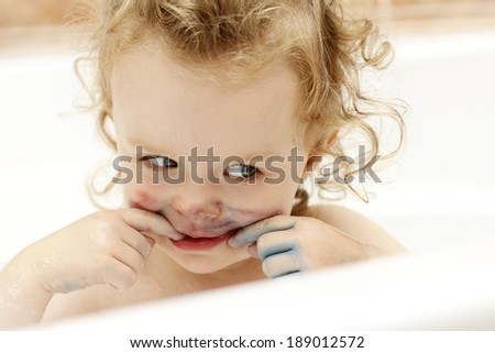 Little dirty toddler having fun while bathing - stock photo