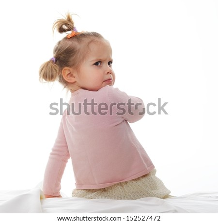 Little displeased girl sitting on bed isolated on white