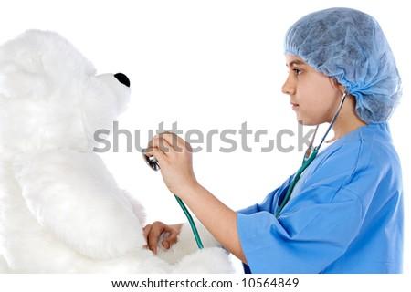 Little doctor examining her teddy - stock photo