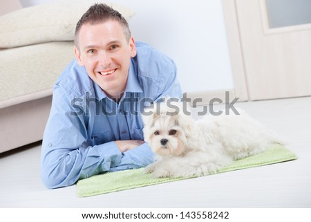 Little dog maltese laying with his owner on the floor in home. Main sharpness focus is on the dog. - stock photo
