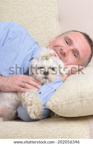 Little dog maltese resting with his owner on the sofa in home - stock photo