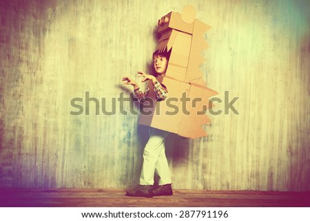 Little dreamer boy playing with a cardboard dragon, dinosaur. Childhood. Fantasy, imagination.  - stock photo