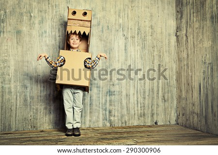 Little dreamer boy playing with a cardboard dragon, dinosaur. Childhood. Fantasy, imagination. - stock photo