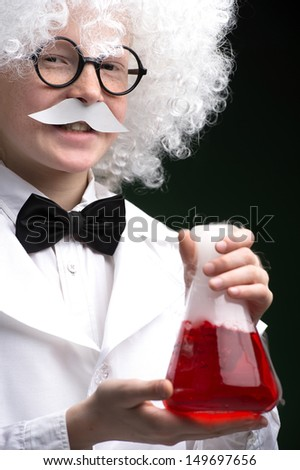 Little Einstein. Cheerful little boy looking like Einstein holding a bottle with red liquid while isolated on black - stock photo