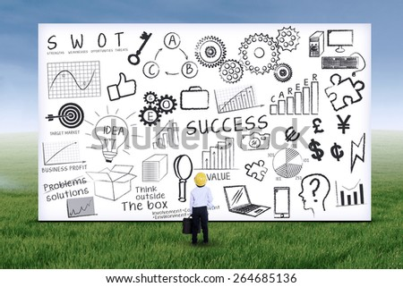 Little engineer looking at business strategy on whiteboard. Shot outdoors - stock photo