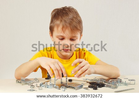 Little engineer plays with mechanical constructor at the table - stock photo