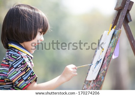 Little European boy painting art board in the park - stock photo