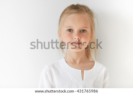 Little European girl in white children clothes looking peacefully at the camera indoors. Calm child standing quietly in restful manner with angelic look and innocent appearance. - stock photo