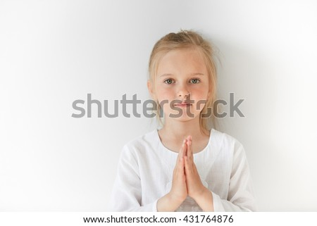 Little European girl in white clothes praying and looking forward with calm and pretty facial expression. Blond child with green eyes watching you peacefully in morning light. - stock photo