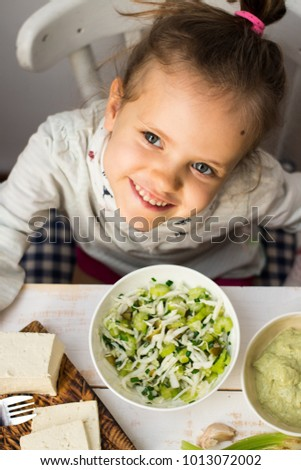 Little european girl smiling and eating fresh green  salad with celery, cucumber, cabbage, onion, greens, herbs and spices. Raw, vegan, vegetarian healthy food concept.