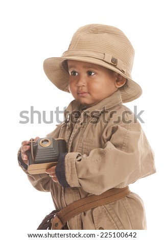 Little explorer.  Adorable toddler dressed in khaki and holding a toy camera.  Isolated on white.