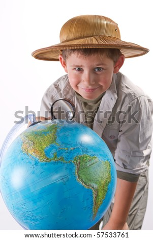 little explorer examining earth globe with magnifying glass - stock photo