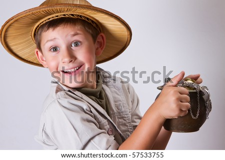 little explorer is amazed by his newest find. A pot of ancient gold coins and jewelry - stock photo