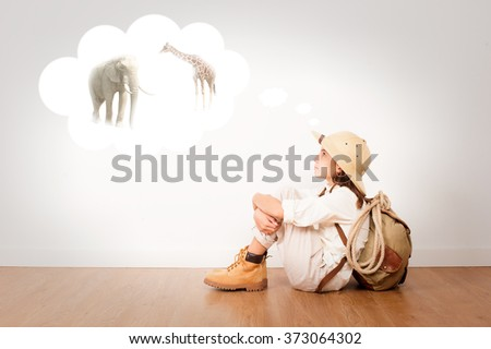 little explorer sitting on a room thinking - stock photo