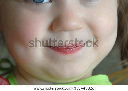 Little eye peeks into image.  This small girl is grinning  mischievously. Closeup image.
