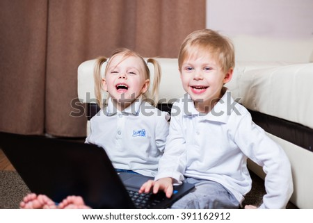 little fair-skinned blond children, a boy and a girl with pigtails sitting with a laptop on the floor, smiling, stormy emotions - stock photo