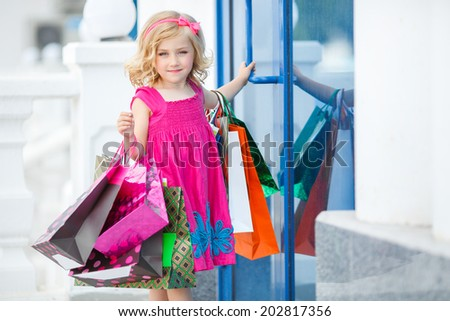 Little fashion girl with packages in a large shopping center. Pretty smiling little girl with shopping bags with thumb up sign in the shop - stock photo
