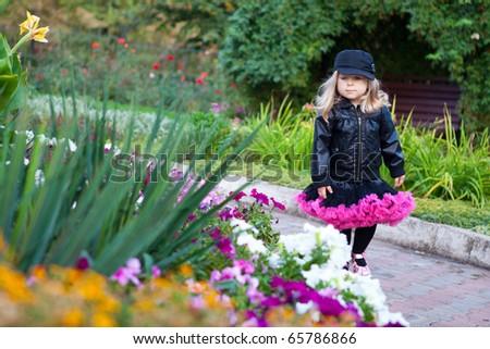 Little fashionable girl walking in flower park - stock photo