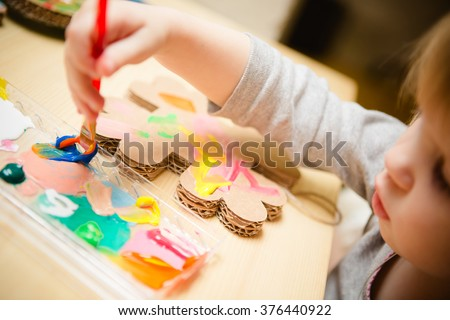 Little female baby painting with colorful paints - stock photo