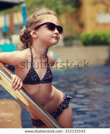Little female model posing in fashion kids sunglasses and swimsuit near swimming pool. Closeup portrait - stock photo