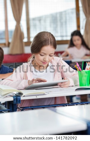 Little female student using digital tablet with friends in background at classroom - stock photo