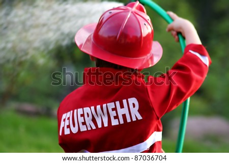 little fire man in the garden with the water hose