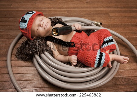 Little Fireman.  Adorable infant dressed as a fireman and asleep in a garden hose.   - stock photo