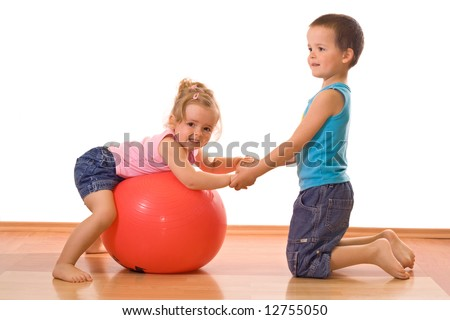 Little firl and boy playing with a large ball on the floor - stock photo