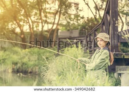 little fisher girl holdin a rod at a river near a bridge - stock photo