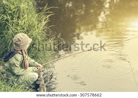 little fisher girl sitting on a river bank with a rod - stock photo