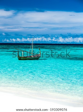 Little fishing boat in blue sea, clear transparent water and white sandy beach on luxury Maldives resort, summer vacation concept - stock photo