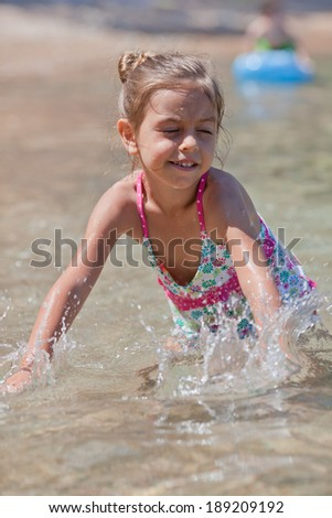 Little five year old girl playing by the sea - stock photo