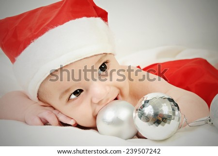 little four month old baby boy wearing red santa hat and red trousers lying on his belly smiling and playing with silver Christmas tree decorative balls - stock photo