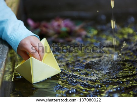 Little four year old boy in a blue outfit playing with paper boats in a small outdoor water fountain