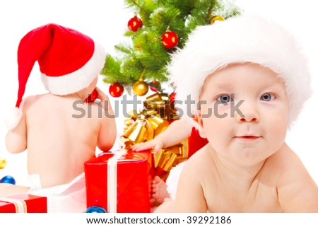 Little friends  sitting beside Christmas tree - stock photo