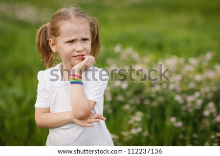 Little frowning girl looking far away, outdoors - stock photo