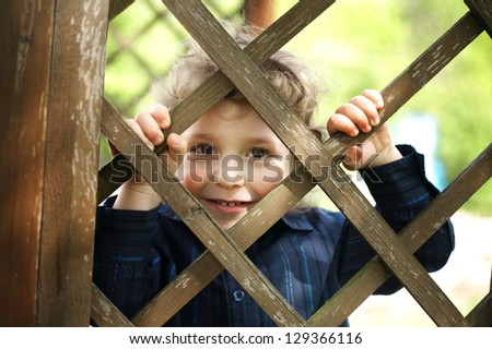 little funny boy behind the fence - stock photo