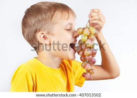 Little funny boy in a yellow shirt eating a grape