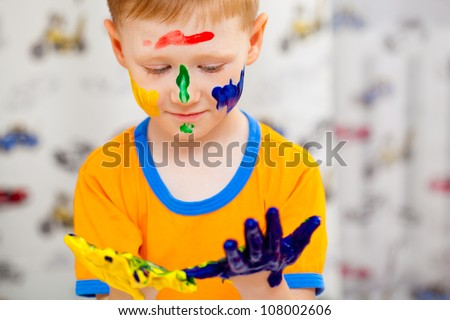 little funny boy looking to his painted hands - stock photo