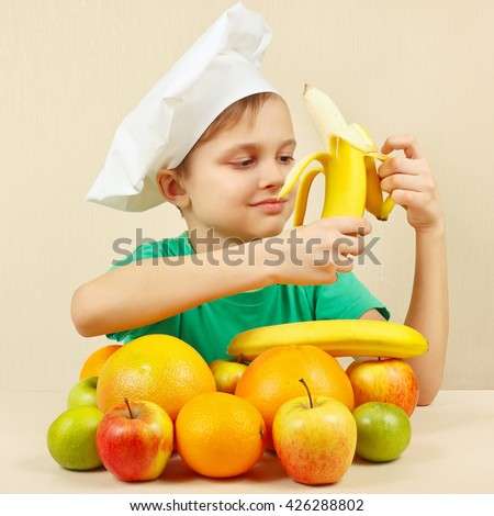 Little funny boy peeling fresh banana at the table with fruits - stock photo