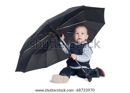 little funny boy sits under black umbrella isolated