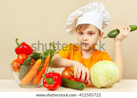 Little funny boy with vegetables at the table - stock photo