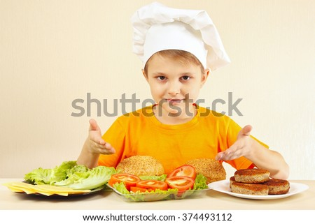Little funny chef at the table with ingredients for a hamburger - stock photo