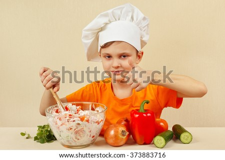 Little funny chef prepared a salad of fresh vegetables