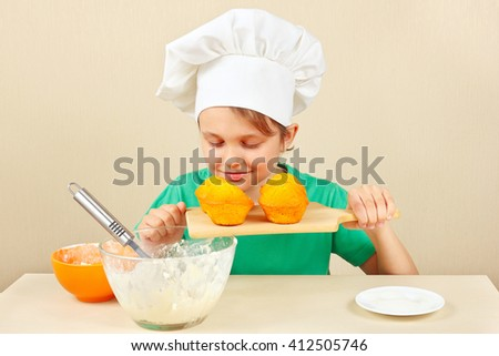 Little funny chef sniffing the aroma of cooked cake - stock photo