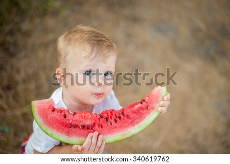 Little funny child eating watermelon outdoors in summer park. Close-up portrait. Shallow DOF. - stock photo