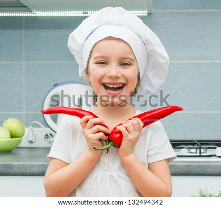 little funny girl in a cap chef in the kitchen with Pepper - stock photo