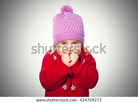 Little Funny girl in cap and red sweater. Isolated on gray background - stock photo